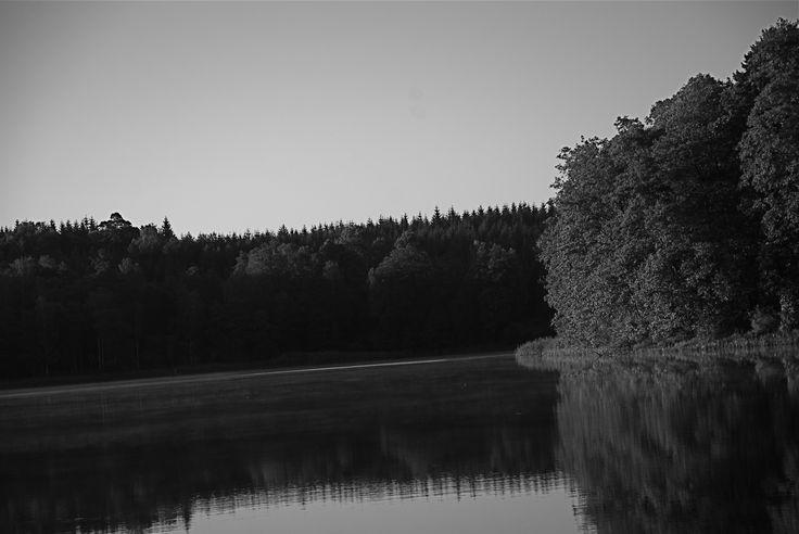 Soluppgång vid Åsljunga med spegelblankt vatten.