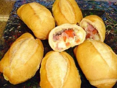 Ingredientes  06 pães franceses 3 xícaras de muzzarela cortada em cubos 300 gr de presunto cortado em cubos. 6 colheres de sopa de azeite 2 tomates sem sementes picados 2 colheres
