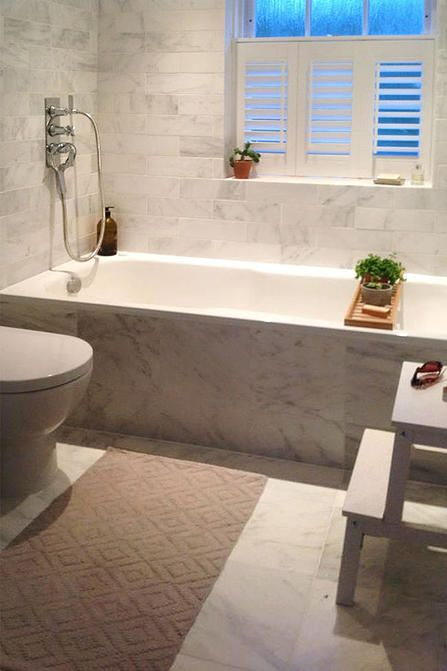 Reyne Design Interior Designer | PORTFOLIO Small bathroom tiled floor to ceiling in white marble tiles from Fired Earth.  Add neutral colours to soften with bath mat and natural wood.