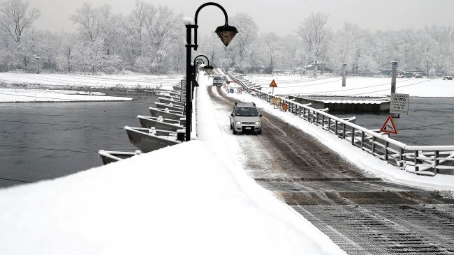 """Cars cross the """"Ponte delle barche"""" (Bridge of the Boats) after a snowfall in Bereguardo, near Milan, Italy, Friday, Dec. 14, 2012."""