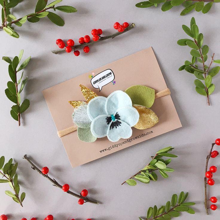 Cette liste est pour une fleur en feutre Pansy dans la couleur bleu pâle, avec une variété de feutre vert et feuilles de paillettes d'or et un brin de tulle de petites paillettes.  Cette conception florale est livré sur une bande de nylon nue--douce, extensible et capable de s'adapter à la plupart des tailles, de la naissance pour les enfants plus âgés, ou une pince crocodile avec poignée sans glissement.  SIL VOUS PLAÎT LIRE BOUTIQUE/POLITIQUES AVANT LACHAT ***  Certaines pièces peuvent...