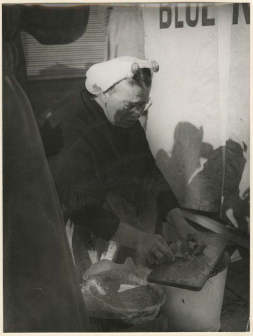 Scheveningse negotiante (visverkoopster) maakt een visje schoon; zij draagt een geplooide muts, een ijzer met boeken, een zwarte omslagdoek en een bont schort. 1954 Marianne Dommisse #ZuidHolland #Scheveningen