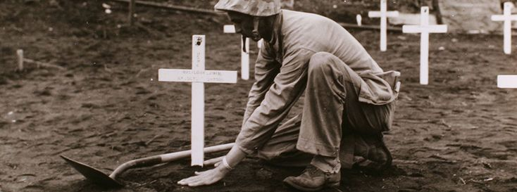 World War two soldier burying a fellow service member