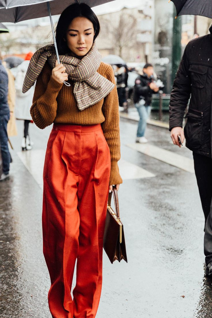 A Stranger in Paris wearing high waisted orange wide legged slacks with a brown khaki coloured jumper tucked in, a large Nougat coloured and slightly patterned scarf tightly circled around the neck.