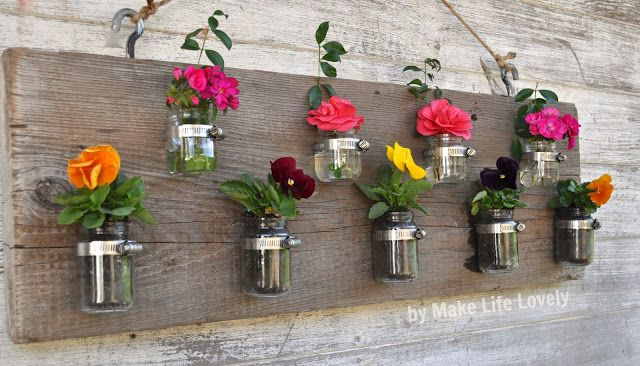 Floral planter display made from baby food jars.  Switch out the flowers with tealights in the winter.