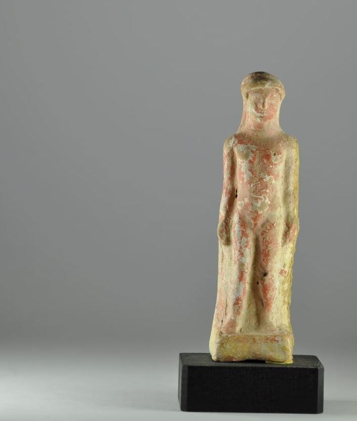 Kouros statue, archaic terracotta statuette of kouros, 5th-4th century B.C. Greek terracotta kouros statue, Greek kouros statue, standing on an integral base, wearing a long garment covering his back and sides, both arms straight down with hands holding the garment, remains of white slip and red color, 10.5 cm high. Private collection