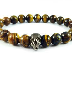 Dizarro to męska biżuteria najwyższej jakości produkowana z kamieni półszlachetnych, srebra, złota oraz kryształów Swarovski™.  Bransoletka wykonana z kamieni 'tygrysie oko' oraz srebrnej, rutenowanej czaszki.Szczegóły:- czaszka z rutenowanego srebra próby 925- bransoletka wkładana na elastycznej gumce- średnica kulek: 8 mm- bransoletka zapakowana w eleganckie, czarne pudełko