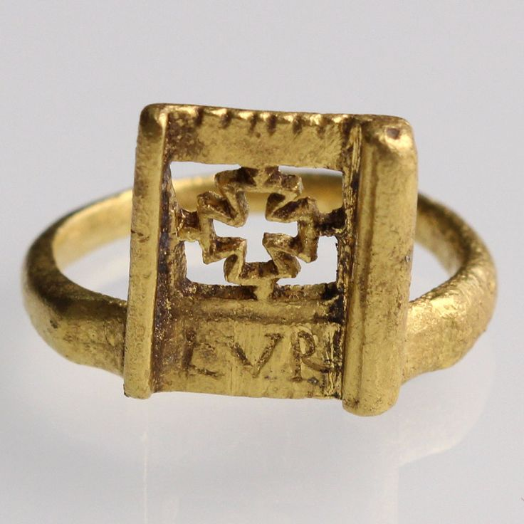 """View 1: Rings with projecting bezels were inspired by bronze key rings, thought to open small boxes (or marriage caskets) in use from the 1st century A.D. up to the early medieval period. The present example (the key element decorative and no longer functional) is unusual because it combines Christian iconography with personal initials. The bezel is engraved with an """"ajouré"""" Greek cross crowning a flat band and inscribed with the letters LVR. The bezel is bordered on each side by a…"""