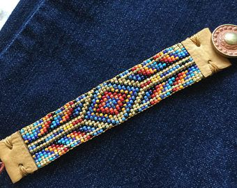 Native American, southwestern, country, hand loomed beaded bracelet, blues, yellow, red, orange, black and gold. Leather, painted button