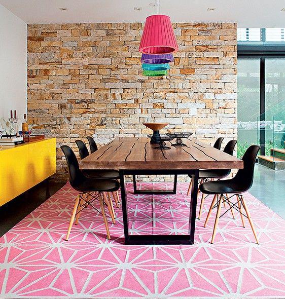Terreno arrematado, a arquiteta Monica Drucker foi encarregada de projetar a casa de 412 m², bem iluminada e com espaços integrados.  A sala de jantar é ligada a outros ambientes da casa e é cheia de cores: rosa no tapete geométrico, amarelo no bufê e vár