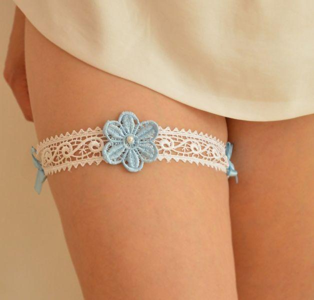Ręcznie wykonana podwiązka składająca się z koronki i kwiatka z gipiury. Kolor biały, kwiatek niebieski z doszytą szklaną perełką. Gumeczka z tyłu jest bardzo elastyczna, a zarazem delikatna.   Dostępna w butiku Madame Allure!
