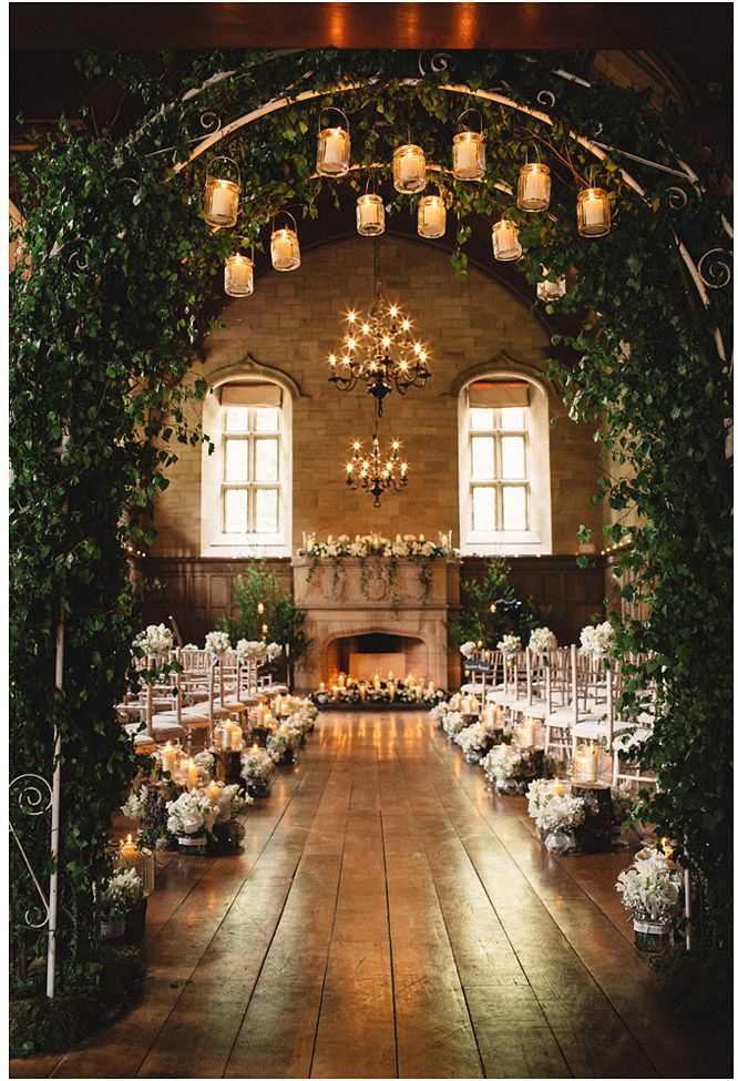 This Scottish wedding was beautifully decorated with a greenery arch and glamorous hanging chandeliers.  Across the fireplace is an assortment of flowers and hanging vines. See more of this elegant Scottish wedding here: http://www.justinscobie.co.uk/achnagairn-house-wedding-photography-ruth-and-iain/