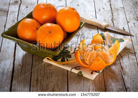 Bowl with honey tangerines and peeled tangerine on antique wood table. by eZeePics Studio, via ShutterStock