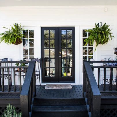 Black deck stain against white house with greenery looks fresh and elegant.