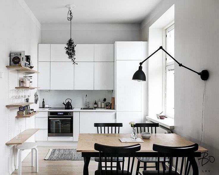 Keittiö loistaa skandinaavista tyyliä. Mustat pinnatuolit pöydän ympärillä, seinävalaisin ja avohyllyt tuovat tilaan upeita yksityiskohtia.