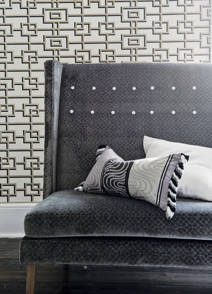 A contemporary grand interpretation of a wing chair, with a high buttoned back from Designers Guild.