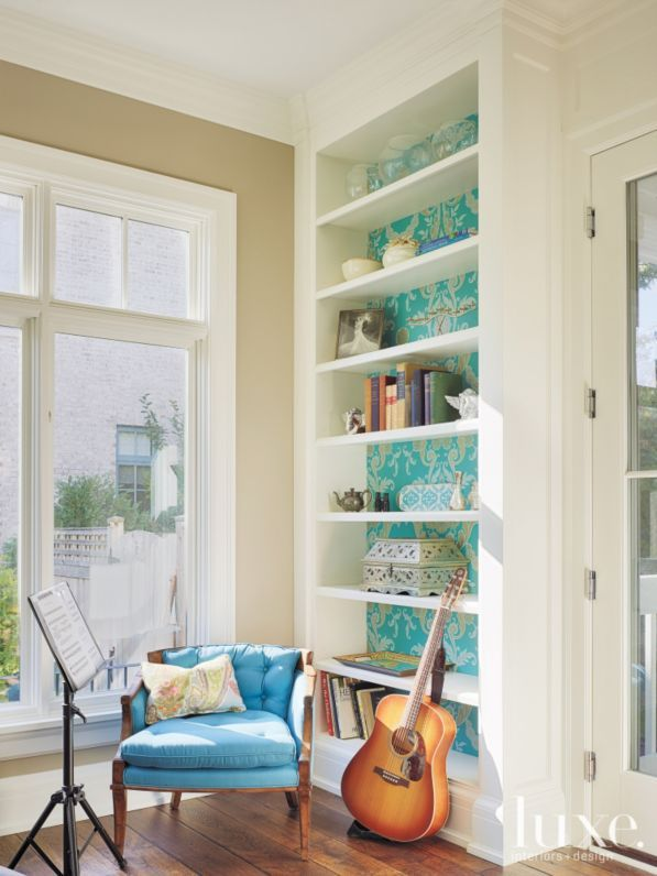 Designers Guild wallcovering lends a touch of whimsy to pre-existing bookshelves