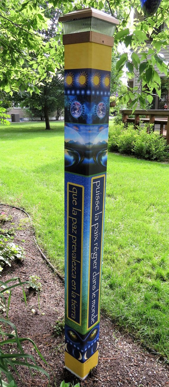 """Our stunning May Peace Prevail on Earth- Garden art peace pole features this well known wish in 4 different languages: English, Spanish, French, and German. The whimsical design and bright colors will add a bit of unique magic to your landscape. This design is brand new. The photos show the artwork. Of course, we apply the art work to a lightweight, weather proof vinyl pole before shipping. With your purchase you will receive a 5x5x64"""" complete pole, complete with solar crown top."""