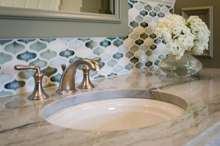 Beautiful glass, mosaic tile in greens and blues brighten the backsplash around this updated traditional bathroom vanity with a stunning marble countertop and simple contemporary fixtures.