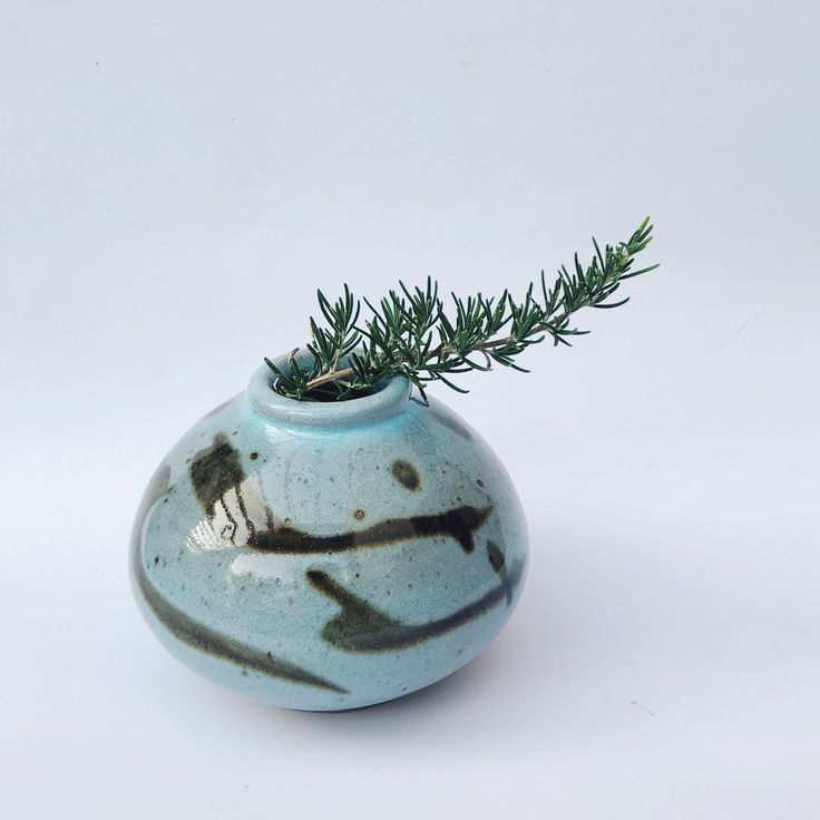 A wide blossom vase. Chun blue glaze with brushes of iron oxide. A slight touch of red/pink on one side as a mysterious effect in the kiln. Wheel-thrown, stoneware glaze, fired to stoneware in reduction. Dimensions (approx):9.5cm tall, 12cm wide.