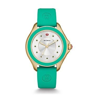 Cape Topaz Gold Tone Green Watch The Cape charms with a Kelly green wear-anywhere silicone strap and a sunray dial sparkling with a green topaz index. Complete with gold touches and the MICHELE logo on the strap, the Cape is both playful and luxurious.