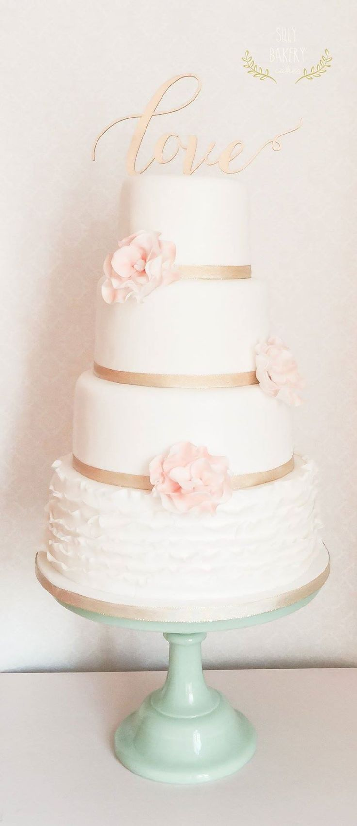 "Soft, cream and pink wedding cake with ""LOVE"" topper from Silly Bakery Cakes"