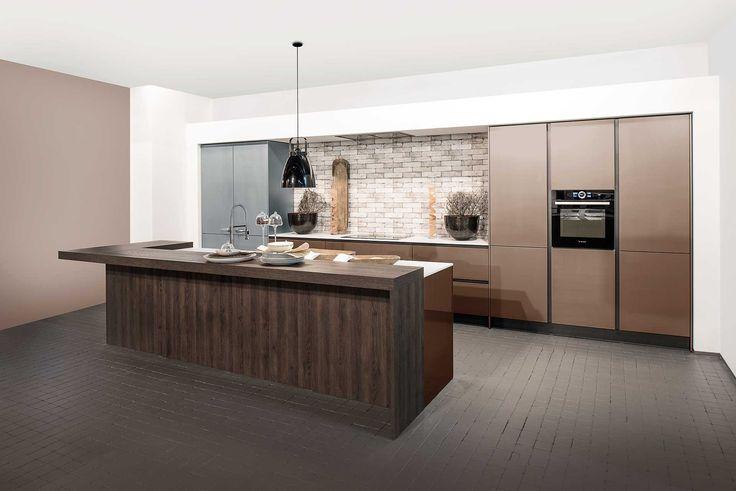 Moderne, bronzen keuken met hout look. Met brons als dé trend kleur van 2016, krijgt deze keuken een unieke look. De keuken is voorzien van een kookplaat, ingebouwd apparatuur en kolomkasten in een brons kleur, dat zich allemaal aan de muur bevindt. Verder heeft deze moderne keuken ook een kookeiland met toog in laminaat met een hout look. De hout kleur van de toog hangt nauw samen met de bronzen keukenkasten, waardoor het geheel warmte uitstraalt. Ook deze moderne keuken is volledig…