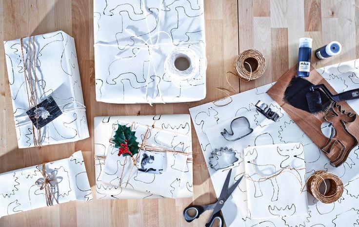 Ein Blick von oben auf verschiedene Päckchen, die auf einem Holztisch liegen. Dort befinden sich auch Gegenstände für das selbst gestaltete Geschenkpapier, u. a. Farbe, Schnur, eine Schere, MÅLA Zeichenpapierrolle und DRÖMMAR Förmchen.
