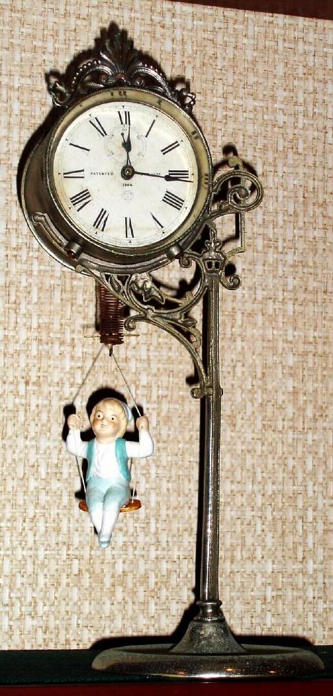 """Gatsbywise -  Ansonia Jumper No. 1 Bobbing Doll Novelty Clock In a nickel plated case with printed paper dial marked """"Patented Dec. 14th 1895 Ansonia Clock Co. Sole Manufacturer, New York, U.S.A."""
