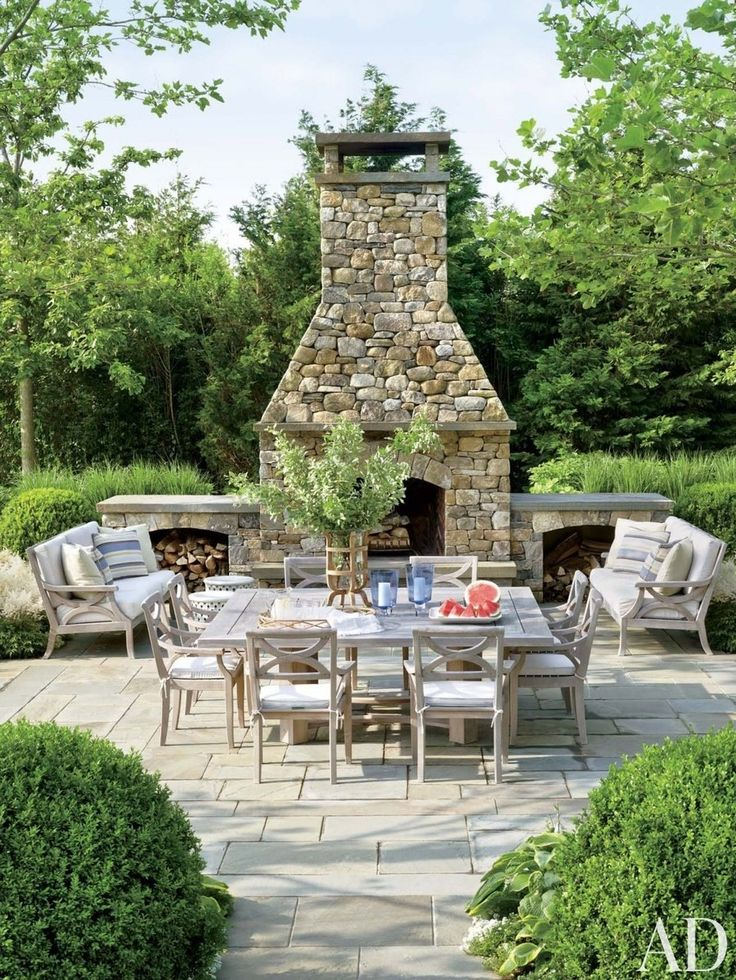 Arranged near the outdoor fireplace of a Southampton home by Carrier and Company Interiors and architect John David Rose are Country Casual sofas and chairs cushioned in a Sunbrella fabric.