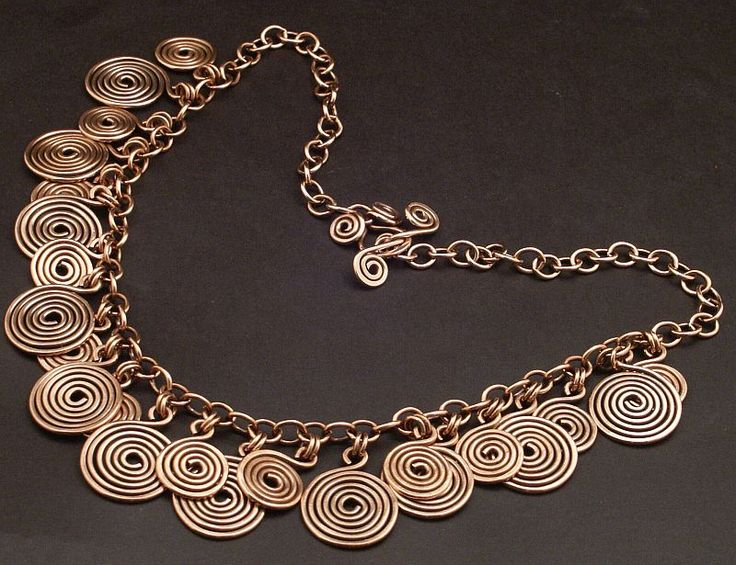 Could be an Art Smith, Alexander Calder or a North African inspired neckpiece. No other source with this Google Image Result for http://4.bp.blogspot.com/-0UgwOIdJT0M/TeQp7ND6I5I/AAAAAAAAAnk/GWDyJeF_0Ro/s1600/spiralnecklace.jpg