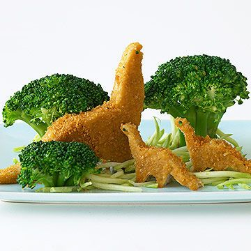 Play with Your Food - Dino-Nuggets - As if kids don't already love chicken nuggets, some companies now make them in the shape of dinosaurs. Tell your child that many dinos ate veggies, then create this jungle scene so he'll chomp on his greens, too. #healthy #snacks