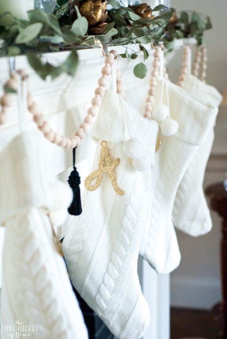 Classic cable knit stockings hung with a DIY wood bead garland, black tassels, and glittered monogram letters