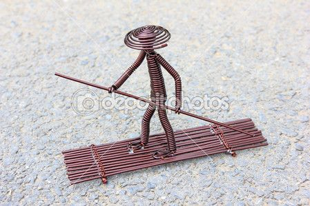 crafts made from copper | Toy crafts boatman made of copper wire on the ground —Photo by lnzyx