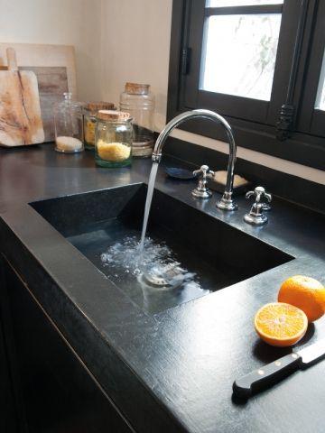 Un évier intégré dans la masse - Une cuisine avec îlot et plan de travail en béton