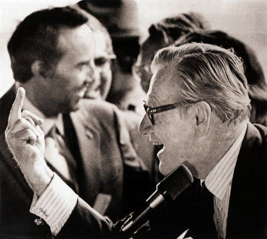 """Sept 16th, 1976, Binghamton, NY — Vice President Nelson Rockefeller gives a crowd of young hecklers an upraised middle finger gesture at the Broome County Airport during a brief stop here while on a campaign trip with Vice Presidential candidate Bob Dole (L, Background, out of focus).  Rockefeller said he was """"responding in kind"""" to the demonstrators. Love it. — Image by © Bettmann/CORBIS.  The """"I could buy and sell you, you little smarmy toad"""" flip."""