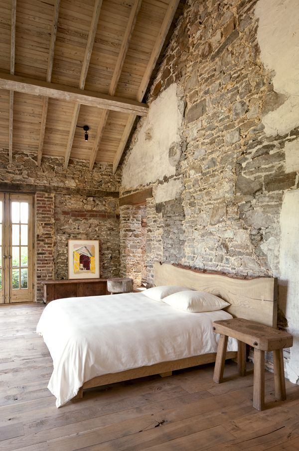 Rustic charm bedroom with a wood ceiling, exposed stone wall and live-edge wood furniture.