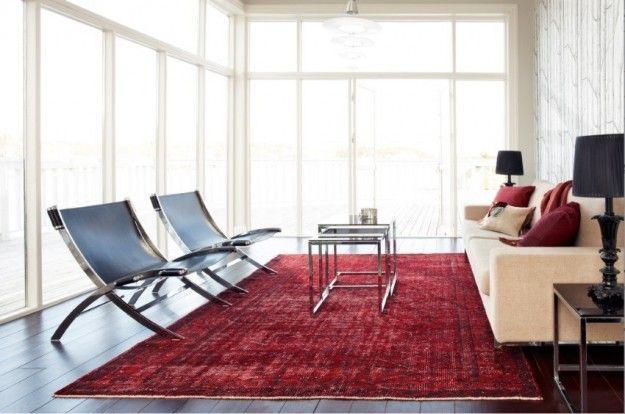 Interior design moderno - Una soluzione dallo stile minimal con tappeto rosso, divano crema e sedie cromate