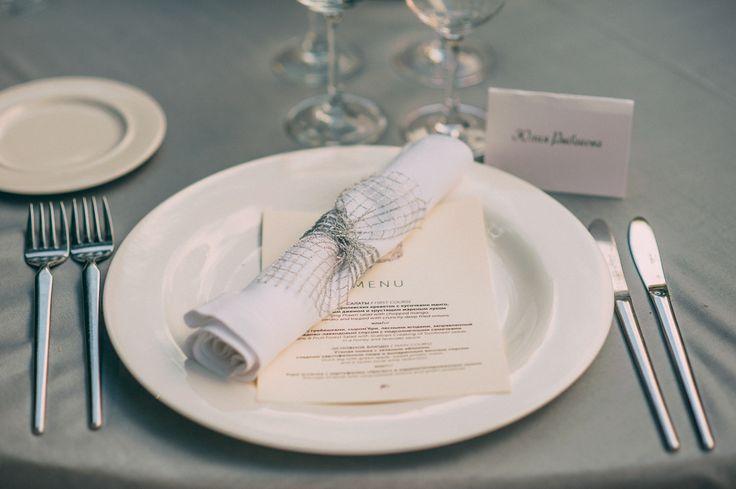 Seating place, napkin decor/ салфетка перевязана серебристой лентой из сетки, под салфеткой меню с гербом молодоженов, на обратной стороне карточки рассадки так же герб молодоженов