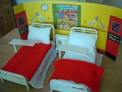Vintage 1980s hospital set to fit Sindy or Barbie (make unknown, but not Pedigree or Mattel). Set comprises: two beds with adjustable headrests; two bed linen sets (white base sheet, duvet, pillow, red cover), two hospital bed tables, side cupboard and cardboard backdrop. There are a few marks here and there, but generally in very good condition for its age
