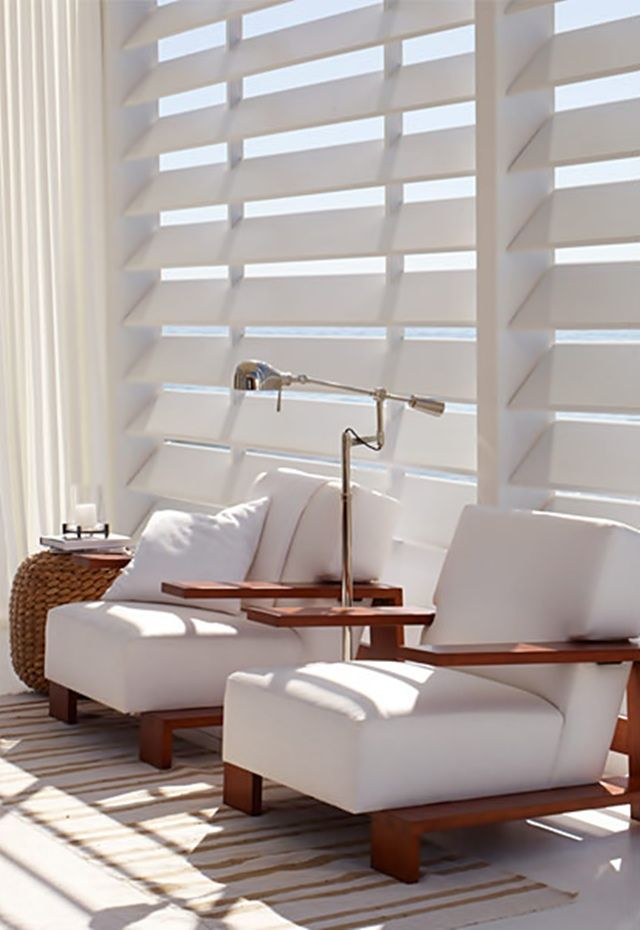 A beach house w/Ralph Lauren chairs, table, and light. White plantation shutters. WIDE....