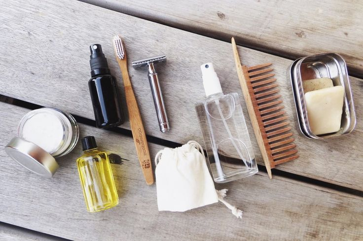 Zero waste travel toiletries | safety razor, wooden comb, bar soap, bamboo toothbrush, face oil, and menstrual cup.