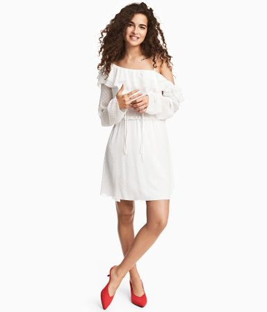 White/dotted. Short dress in crinkled chiffon with a printed pattern. Ruffles at top, one open shoulder with narrow shoulder strap, and long sleeves with