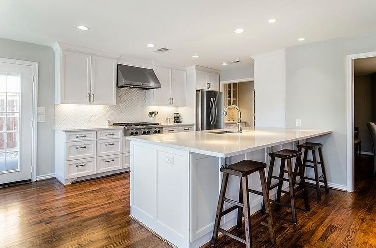 white shaker cabinets with quartz countertops. chic white kitchen features shaker cabinets paired with quartz countertops and a herringbone tile backsplash. s