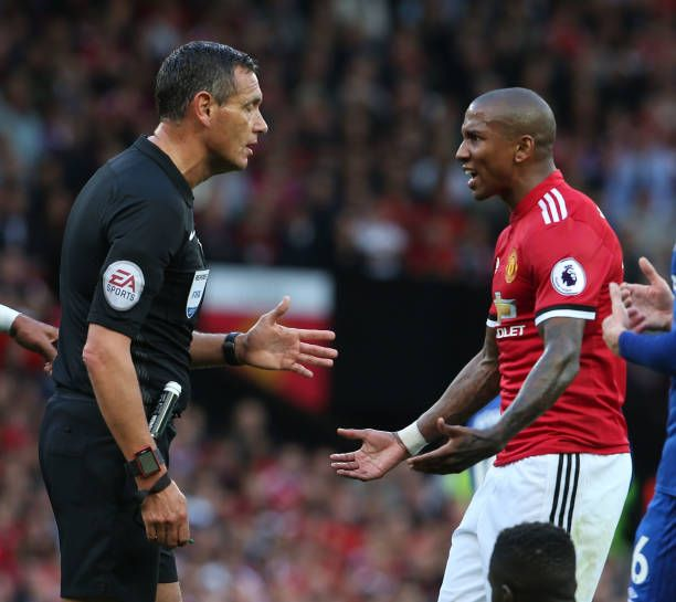 Referee Andre Marriner talks to Ashley Young of Manchester United during the Premier League match between Manchester United and Everton at Old...