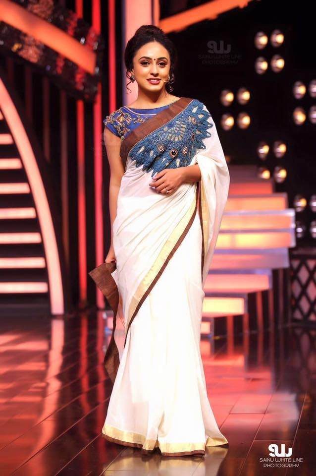 Pearly maaney in white peacock detailed saree with cream and brown border costume by parvathy