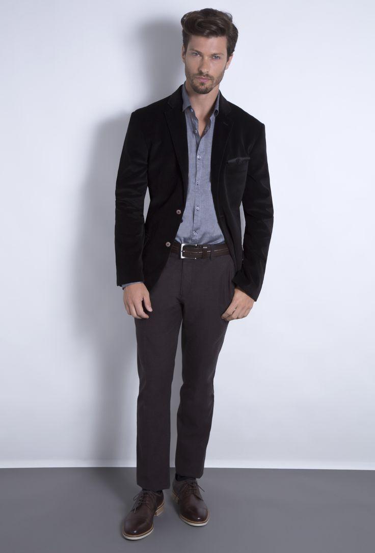 Camisa cinza fio a fio sobreposta por blazer preto de veludo e combinada à calça marrom de alfaiataria em flanela. O sapato brogue no mesmo tom da calça alonga as pernas.