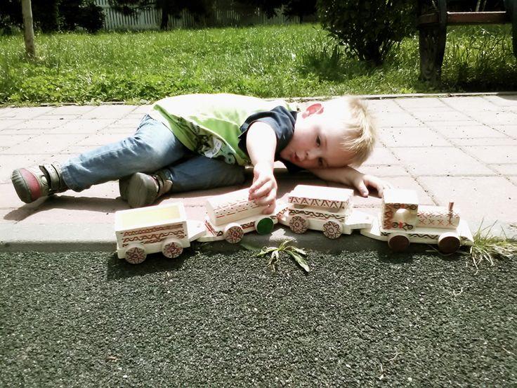 """Luca a primit un trenuleț din lemn natur, de brad, cu trei vagoane și, împreună cu mama lui, l-a colorat. De atunci trenulețul a devenit jucăria sa preferată. În parc, bordura aleii este linia de tren. Luca e foarte încântat că locomotiva are coș pentru fum și cât timp trenulețul merge, Luca îl ajută cu un prelung """"Uuuuu!"""".  Luca are doi ani și cinci luni.  Trenulețul poate fi cumpărat de pe www.ruralart.ro. Luca, nu."""