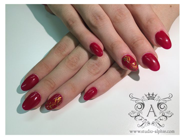 All red oval nail form with gold pattern.