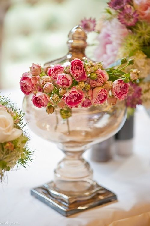 Small pink rose buds in antique glass container #weddingflowers #centerpiece